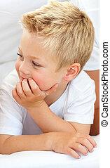 Portrait of a cute blond boy lying on a bed