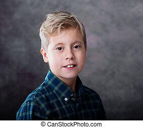 Portrait of a cute blond teenage boy dressed in a plaid shirt