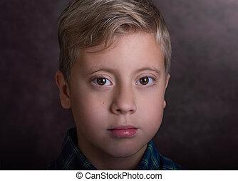 Portrait of a cute blond teenage boy dressed in a plaid shirt.