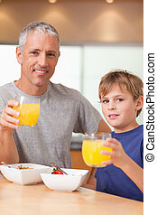Portrait of a cute boy and his father having breakfast