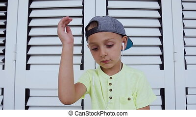 Portrait of a cute boy wearing t-shirt and cap who is listen favorite music on smartphone with headphones, dancing shaking his head over white background. Concept of emotions.