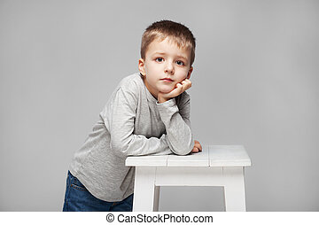 Portrait of a cute boy with standing at the chair in the photostudio