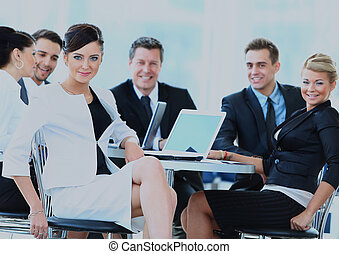 Portrait of a cute business woman smiling with colleagues.