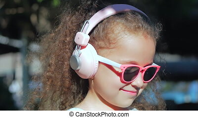 Portrait of a Cute Child, a Wonderful Little Beautiful Girl in a White Dress With Pink Glasses and Pink Headphones, Looking at the Camera, Listening to Music. Concept Happy Childhood.