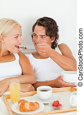 Portrait of a cute couple eating breakfast in their bedroom