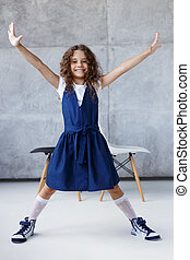 Portrait of a cute curly girl, in dress posing in the studio with her hands and feet sideways, over concrete background.