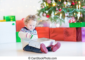Portrait of a cute curly toddler girl opening her Christmas pres