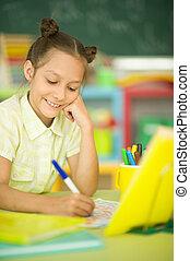 Portrait of a cute girl doing homework