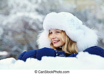 portrait of a cute girl in the winter. playing snow teen outdoors.