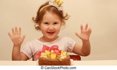 Portrait of a cute girl on her birthday and party. Happy child enjoys a holiday cake and claps her hands