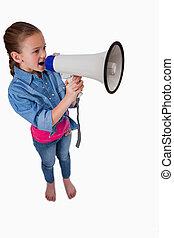 Portrait of a cute girl speaking through a megaphone against...