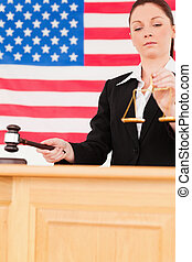 Portrait of a cute judge knocking a gavel and holding scales of justice with an American flag in the background