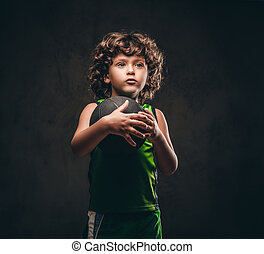 Portrait of a cute little basketball player in sportswear holding the ball in a studio. Isolated on the dark textured background.