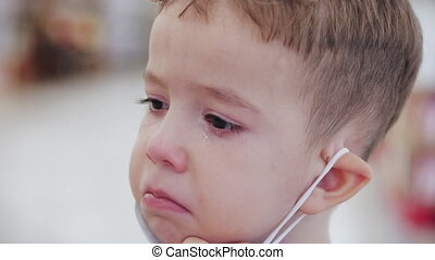 Portrait of a cute little boy a child in a mask from viruses of the coronavirus epidemic cries upset wipes eyes with his hands looks at the camera, tears crying frightened upset child looks around.