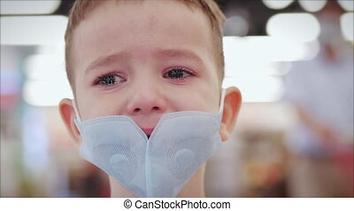 Portrait of a cute little boy child in a mask from viruses of an epidemic coronavirus in a store with a parent, cries frightened upset screams, wipes his eyes with his hands, the child looks around