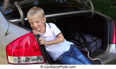 Portrait of a cute little boy in the trunk of the car. Family trip. Road.