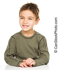 Portrait of a cute little boy sitting at table, isolated over white
