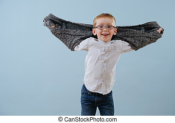 Portrait of a cute little ginger boy in glasses playing with sweater over blue