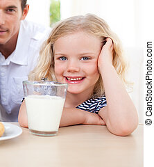 Portrait of a cute little girl and her father in the kitchen