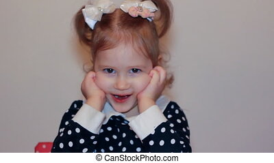 Portrait of a cute little girl close-up. Happy child smiling and looking at camera and and holds his hands near his face. Beautiful face of the kid