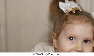Portrait of a cute little girl close-up. Happy child smiling and looking at camera. Beautiful face of the kid