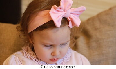 Portrait of a cute little girl closeup, whose eyes are lowered downwards looking playing the game. Funny child and looks at the phone screen and plays downloaded application on a smartphone. closeup