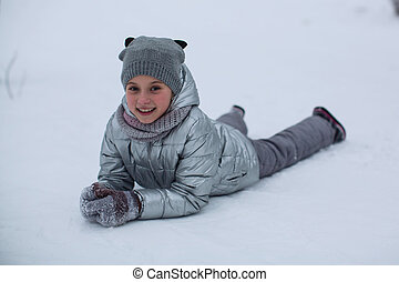 Portrait of a cute little girl in the winter outdoors in the snow.