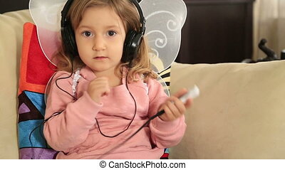 Portrait of a cute little girl listening to music