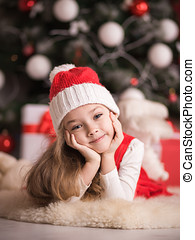 Portrait of a cute little girl on a christmas tree background.