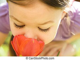 Portrait of a cute little girl smelling flowers