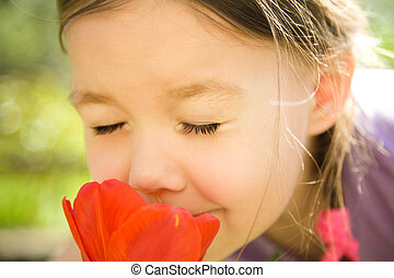 Portrait of a cute little girl smelling flowers outdoors