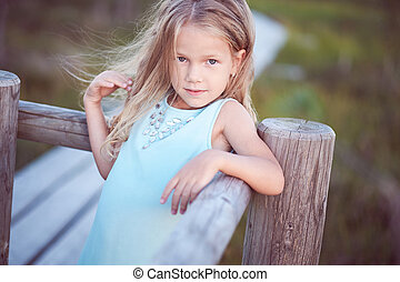 Portrait of a cute little girl, standing outdoors while leaning on a wooden fence.