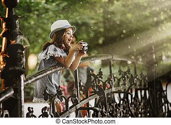 Portrait of a cute little girl taking a photo