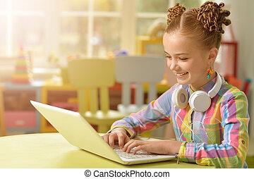 cute little girl using laptop