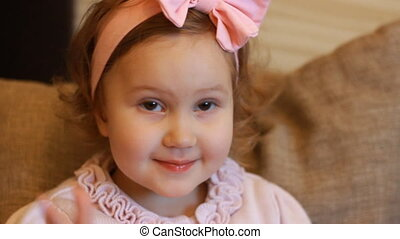 Portrait of a cute little girl who smiles and looks at the camera. Face of a smiling child closeup.