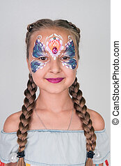 Portrait of a cute little girl with a painted face on a white background