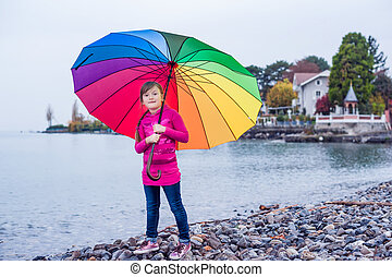Portrait of a cute little girl with big colorful umbrella