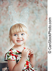 Portrait of a cute little girl with bunny ears.