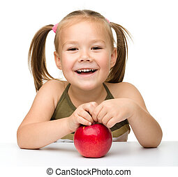 Portrait of a cute little girl with red apple
