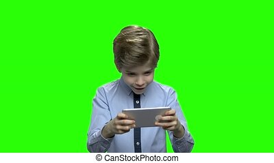 Portrait of a cute little kid playing games on smartphone.