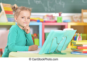 Portrait of a cute schoolgirl doing homework