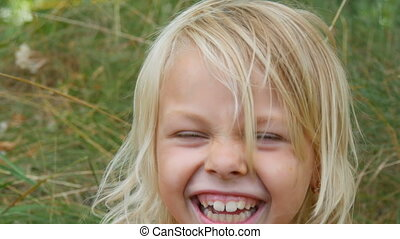 Portrait of a cute smiled and laugh blue-eyed blonde seven-year-old girl with a dirty face child on a street outside the city on a summer day