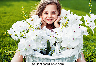Portrait of a cute smiling child with a flower basket