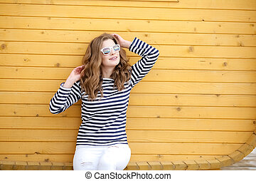 Portrait of a cute smiling girl in white jeans and a striped T-shirt near a Yellow wall