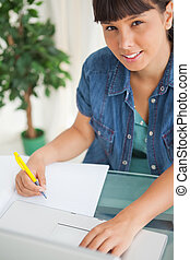 Portrait of a cute smiling student doing her homework