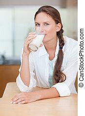Portrait of a cute woman drinking milk
