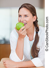 Portrait of a cute woman eating an apple