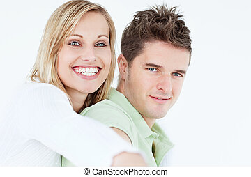 portrait of a cute woman hugging her boyfriend smiling at the camera against a white background