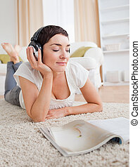 Portrait of a cute woman reading a magazine while enjoying some music in her living room