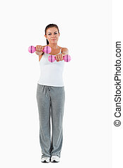 Portrait of a cute woman working out with dumbbells